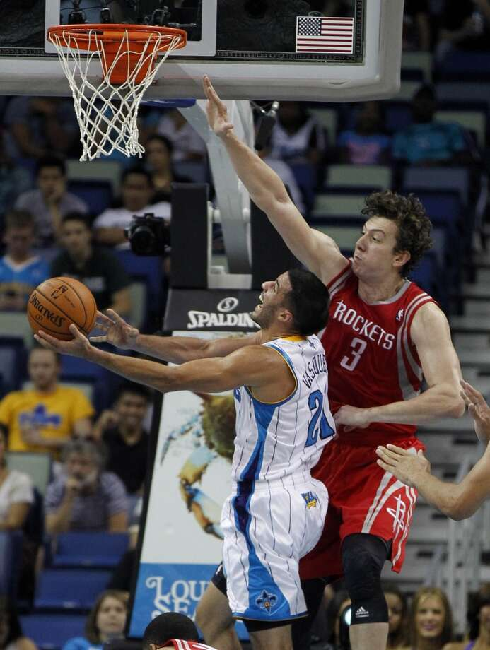 New Orleans Hornets point guard Greivis Vasquez, left, drives to the basket against Houston Rockets center Omer Asik (3) in the first half of an NBA basketball game in New Orleans, Wednesday, Oct. 24, 2012. (AP Photo/Gerald Herbert) (Associated Press)
