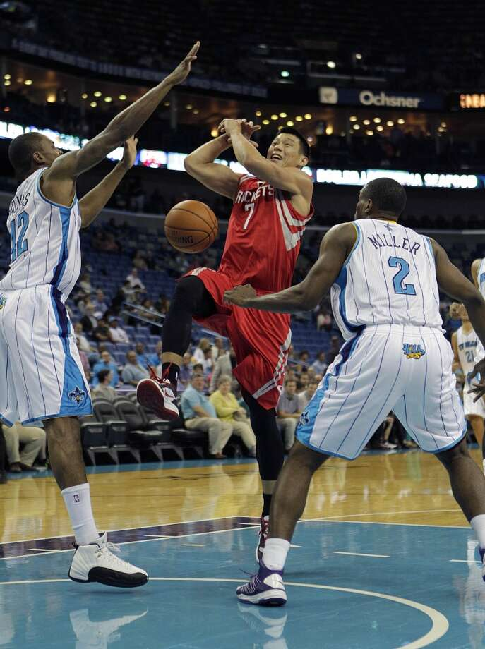 Houston Rockets point guard Jeremy Lin (7) drives to the basket between New Orleans Hornets small forwards Lance Thomas (42) and Darius Miller (2) in the first half of a preseason NBA basketball game in New Orleans, Wednesday, Oct. 24, 2012. (AP Photo/Gerald Herbert) (Associated Press)