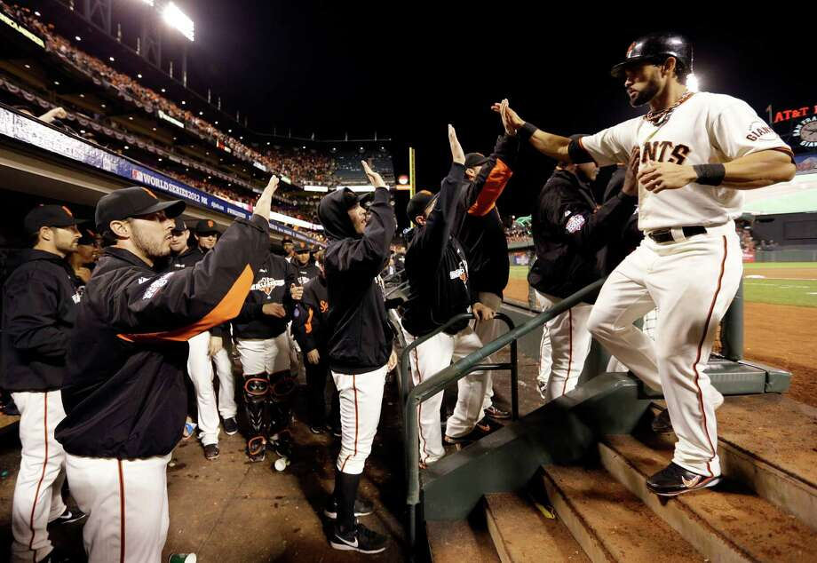 San Francisco Giants' Angel Pagan is congratulated in the dugout after scoring during the seventh inning of Game 1 of baseball's World Series against the Detroit Tigers Wednesday, Oct. 24, 2012, in San Francisco. (AP Photo/David J. Phillip) Photo: David J. Phillip, Associated Press / AP