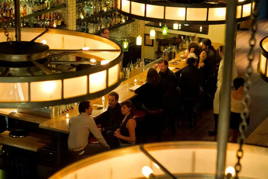 Above right: The bar at Lolinda Steakhouse in San Francisco, Calif., is seen on Friday, October 19th, 2012. Right: Chef Alejandro Morgan looks over a steak leaving the kitchen Photo: John Storey, Special To The Chronicle