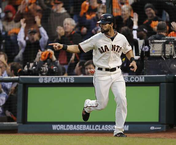 Giants' center fielder Angel Pagan points back to Marco Scutaro after scoring on a Scutaro single in the third inning during game 1 of the World Series at AT&T Park on Wednesday, Oct. 24, 2012 in San Francisco, Calif. Photo: Michael Macor, The Chronicle
