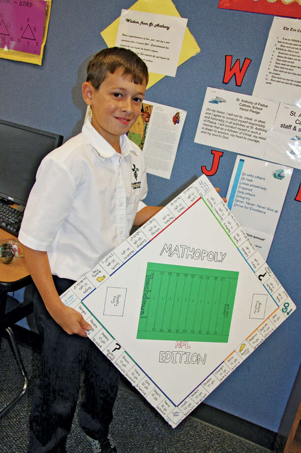 Blake Perry, 11, displays the board game he made to help students with math.