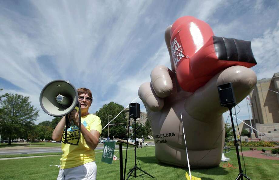"FILE - In this Wednesday, Sept. 7, 2011, file photo, Sierra Club volunteer Becky Williams uses a megaphone in Little Rock, Ark., at a rally against a coal-fired power plant near a large inflatable depicting a hand holding an asthma inhaler. Patients who use respiratory inhalers will be able to recycle the devices for the first time in the U.S., according to British drugmaker GlaxoSmithKline PLC, which is launching its ""Complete the Cycle"" program Wednesday, Oct. 24, 2012, in drugstores in 31 cities.   (AP Photo/Danny Johnston, File) Photo: Danny Johnston"