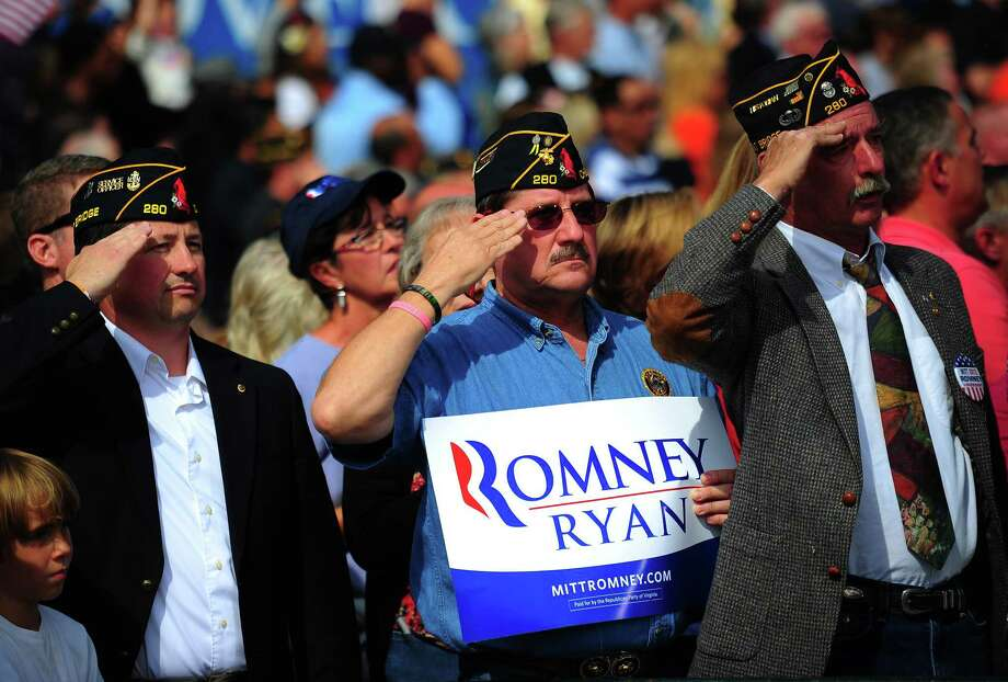 (FILES) US military veterans salute while attending a Republican presidential candidate Mitt Romney rally at The Grove, in Chesapeake, Virginia, October 17, 2012. US President Barack Obama and Mitt Romney race through final preparations ahead of their final debate on October 22, 2012, looking to exploit cracks in each other's foreign policy platforms two weeks before an election set to go down to the wire. AFP PHOTO/Emmanuel DUNAND/FILESEMMANUEL DUNAND/AFP/Getty Images Photo: EMMANUEL DUNAND, AFP/Getty Images / AFP