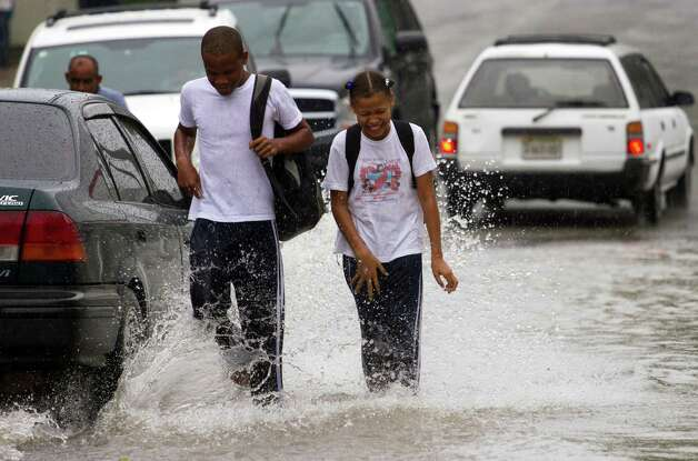 Dominican school children walk in the flooded streets of Santo Domingo before the arrival of Hurricane Sandy on October 24, 2012. The category one hurricane on the five-level Saffir-Simpson scale was forecast to dump up to 12 inches of rain across Jamaica, Haiti, the Dominican Republic, Haiti and eastern Cuba. AFP PHOTO/ERIKA SANTELICESERIKA SANTELICES/AFP/Getty Images Photo: ERIKA SANTELICES, AFP/Getty Images / afp