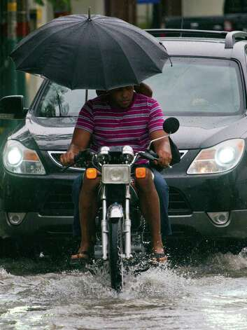 Locals ride a motorbike in a flooded street of Santo Domingo before the arrival of Hurricane Sandy on October 24, 2012. The category one hurricane on the five-level Saffir-Simpson scale was forecast to dump up to 12 inches of rain across Jamaica, Haiti, the Dominican Republic, Haiti and eastern Cuba. AFP PHOTO/ERIKA SANTELICESERIKA SANTELICES/AFP/Getty Images Photo: ERIKA SANTELICES, AFP/Getty Images / afp