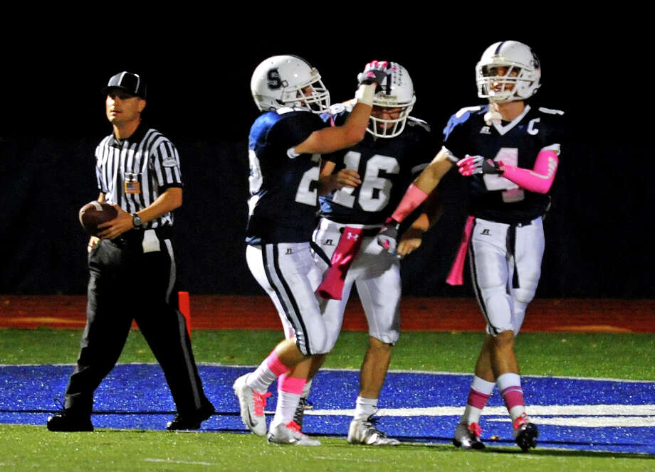 Teammate celebrate with QB Jack Massie, center, after bringing in a touchdown, during football action in Westport, Conn. on Friday October 19, 2012. Photo: Christian Abraham