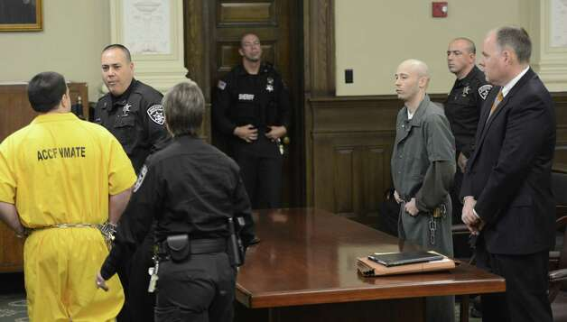 Matthew Cahn, left, father of the deceased child, leaves the courtroom after giving a victim impact statement as defendant  Robert Hayden watches. Hayden was  sentenced for killing Cahn's child Avery Cahn while babysitting the child. Hayden's sentence was imposed by Rensselaer County Judge Andrew Ceresia in the Rensselaer County Courthouse in Troy, N.Y. Oct 25, 2012.  (Skip Dickstein/Times Union) Photo: SKIP DICKSTEIN / 00019838A