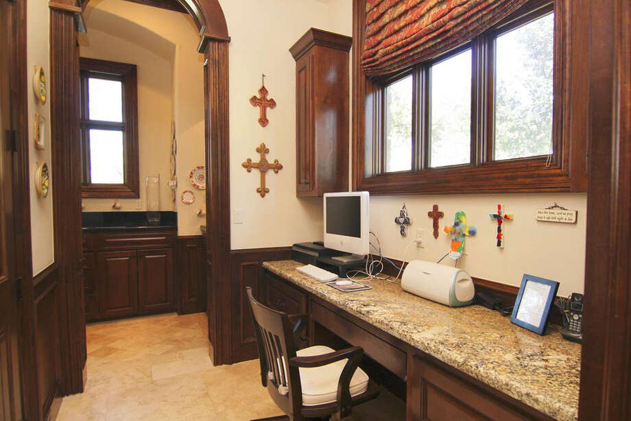 This additional study space has a granite countertop and an arched wooden doorway. Photo: Better Homes And Gardens Real Estate