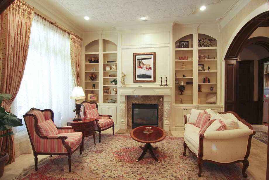 The family room includes a fireplace, crown molding and a patterned ceiling. Photo: Better Homes And Gardens Real Estate