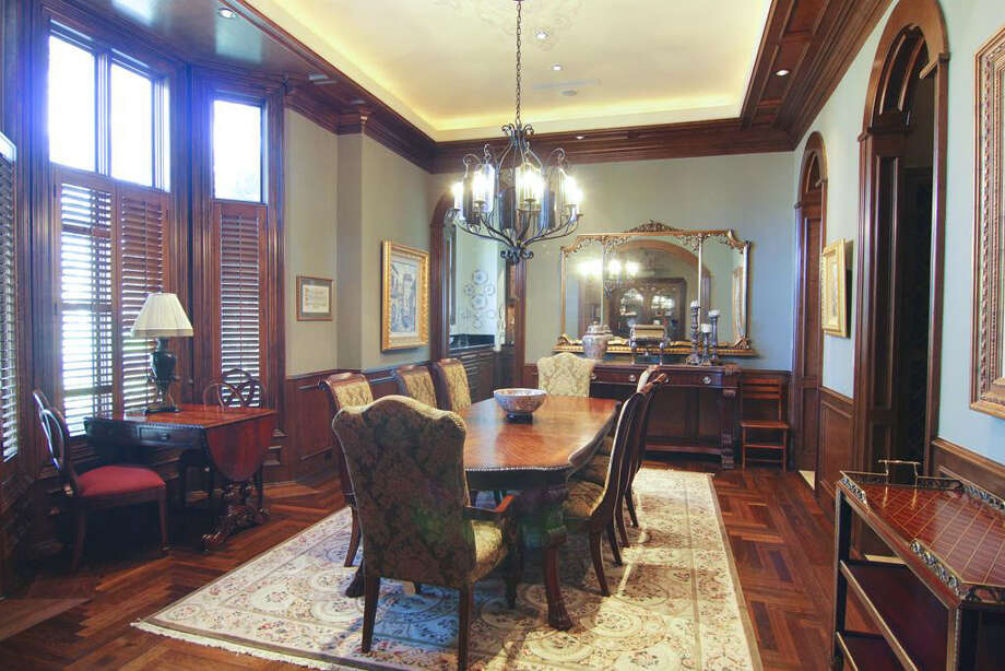 The formal dining room has wainscoting, hardwood floors and arched doorways. Photo: Better Homes And Gardens Real Estate