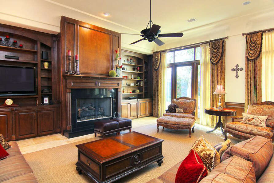 The formal living room has solid wood cabinets and buttery-yellow walls.