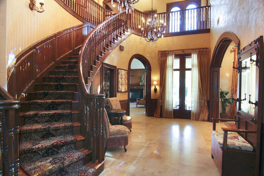 The foyer has marble floors and second floor balconies. Photo: Better Homes And Gardens Real Estate