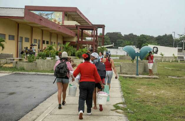 "Citizens of Bayamo, 740 km east of Havana, move to safer places on October 24, 2012 as the residents of eastern Cuba prepare for the arrival of Hurricane Sandy. Hurricane conditions were expected in eastern Cuba in the evening, with the storm set to pass over the Bahamas Thursday and Friday, according to the NHC, which warned that conditions were ""deteriorating"" in Jamaica.        AFP PHOTO/STRSTR/AFP/Getty Images Photo: STR, AFP/Getty Images / AFP"