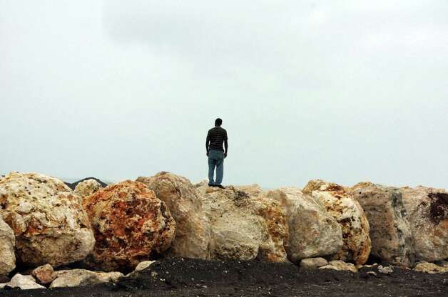 A man stands on boulders placed as a barrier to help prevent flooding of the seaside road that leads to the international airport as Hurricane Sandy approaches Kingston, Jamaica, Wednesday, Oct. 24, 2012. Hurricane Sandy pounded Jamaica with heavy rain as it headed for landfall near the country's most populous city on a track that would carry it across the Caribbean island to Cuba, and a possible threat to Florida. Photo: Collin Reid, AP / AP