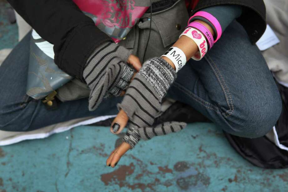 Tiffany Wilson adjusts her gloves in the morning cool after arriving at 8:30 a.m. Thursday morning to wait in line for the opening of the Times Square Microsoft store on October 25, 2012 in New York City. The official store opening was scheduled for Thursday night ahead of Friday's release of the long-awaited Microsoft Surface tablets and the Windows 8 operating system. Photo: John Moore, Getty Images / 2012 Getty Images