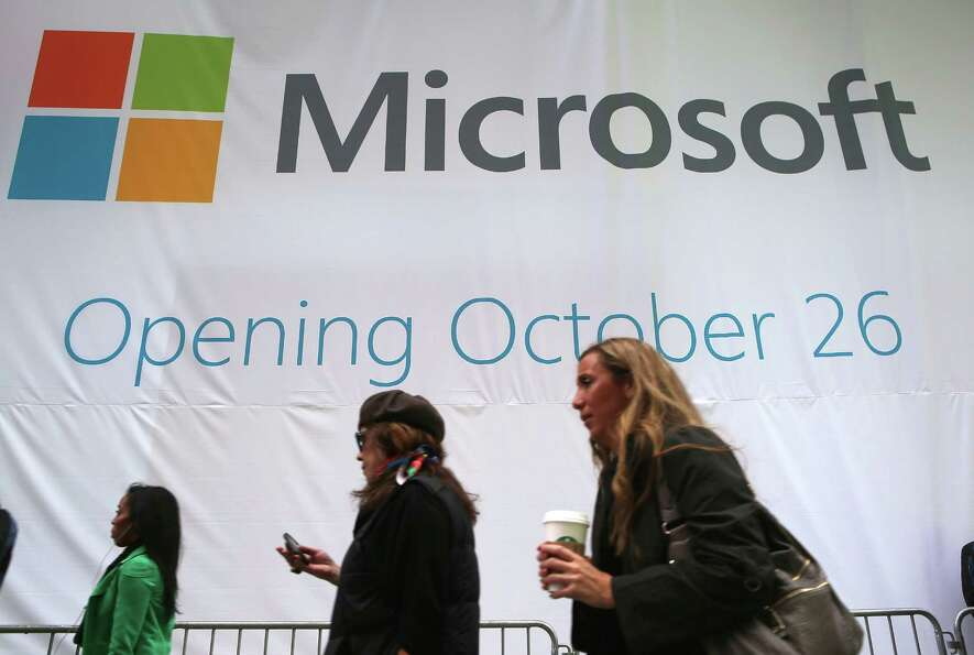 Pedestrians pass the soon-to-be-unveiled Microsoft store in Times Square on October 25, 2012 in New