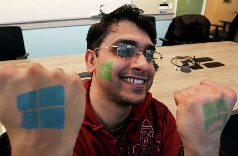 Microsoft engineer Rajas Patil smiles as he displays for the photographer temporary tattoos with the company's logo during an event unveiling the new Microsoft Windows 8 operating system 