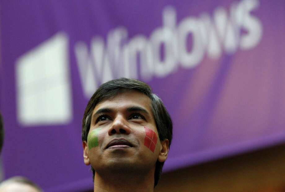Microsoft program manager Joseph Morris, sporting a pair of company temporary-tattoo logos on his face, looks on during an event unveiling the new Microsoft Windows 8 operating system Thursday, Oct. 25, 2012, at the company's headquarters in Redmond, Wash. Photo: AP