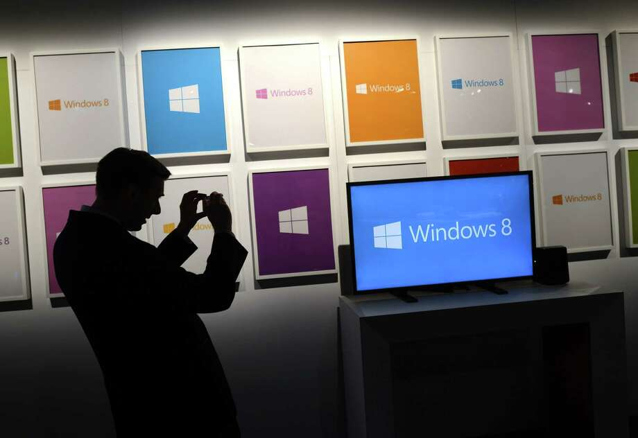A reporter takes photos before the start of a press conference to  officially launch Windows 8 at Pier 57 in New York October 25, 2012. Photo: TIMOTHY A. CLARY, AFP/Getty Images / 2012 AFP