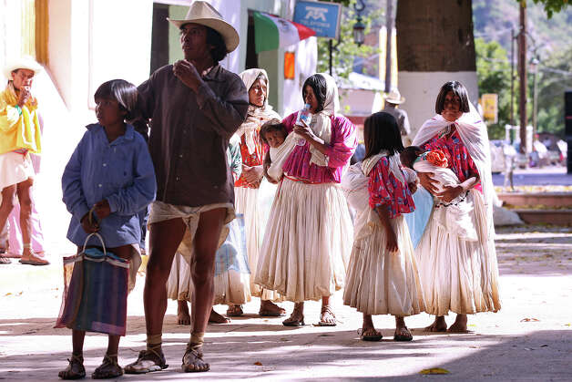 Some Tarahumara gather for government handouts in Batopilas, Mexico. The bimonthly handouts by Ministry of Social Development start at around 800 pesos and rise according to a family's size and other factors. Photo: Jerry Lara, San Antonio Express-News / San Antonio Express-News