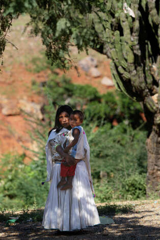 "Chayo Torres, 25, holds her infant son, Daniel, in the settlement of El Arenal de Los Lupes near Batopilas, Mexico, Sunday, Oct. 7, 2012. She had three children, she said, ""uno se me acabo,"" meaning died. The Tarahumara have historically lived through cyclical waves of hunger and Torres had no doubt her community would soon need help. ""It's very bad. I just traded some chili pequins for a kilo of flour. We have some squash and a little corn, but no beans."" Photo: Jerry Lara, San Antonio Express-News / San Antonio Express-News"