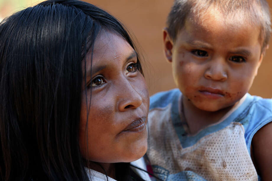 """Chayo Torres, 25, holds her infant son, Daniel, in the settlement of El Arenal de Los Lupes near Batopilas, Mexico, on Oct. 7, 2012. She had three children, she said, """"uno se me acabo,"""" meaning died. The Tarahumara have historically lived through cyclical waves of hunger, and Torres had no doubt her community would soon need help. """"It's very bad. I just traded some chili pequins for a kilo of flour. We have some squash and a little corn, but no beans."""" Photo: Jerry Lara, Staff Photographer / San Antonio Express-News"""