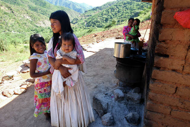 A Tarahumara family's interest is piqued by a visit from a Batopilas government official to El Arenal de Las Lupes settlement in the Mexican Sierra Tarahumara. Photo: Jerry Lara, San Antonio Express-News / San Antonio Express-News