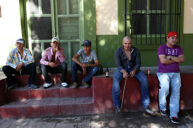 "After a night of partying, young men hang out at the plaza in Batopilas, Mexico, Sunday, Oct. 7, 2012. The town, at the bottom of Batopilas Canyon in Chihuahua, held the annual public address by Mayor Leonel Hernandez. With it came free food and music until late Saturday. The once-popular tourist destination remains largely untouched by modernity. With the drug war crisis affecting the area and the rest of the country, tourism has come to a standstill. ""It's a hugh crisis for Batopilas. Tourism supports a lot of people. It's very severe and the government can do very little,"" said city administrator Rafael Gastelum. Photo: Jerry Lara, San Antonio Express-News / San Antonio Express-News"