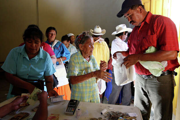 "People gather for government handouts in Batopilas, Mexico, Saturday, Oct. 6, 2012. The bi-monthly handouts by Ministry of Social Development, (SEDESOL), start at around 800 pesos and rises according to family size and other factors. The town, at the bottom of Batopilas Canyon in Chihuahua, was once a popular tourist destination. With the drug war crisis affecting the area and the rest of the country, tourism has come to a standstill. ""It's a hugh crisis for Batopilas. Tourism supports a lot of people. It's very severe and the government can do very little,"" said city administrator Rafael Gastelum. Photo: Jerry Lara, San Antonio Express-News / San Antonio Express-News"