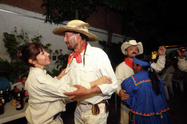 Julia Lopez dances with, Pedro Pallarez, during a dinner for trail riders in Batopilas, Mexico, Monday, Oct. 8, 2012. They was part of the trail ride retracing a 350-mile, 15-day torturous route followed a century ago by muleskinners hauling silver ingots to the city of Chihuahua. Photo: Jerry Lara, San Antonio Express-News / San Antonio Express-News