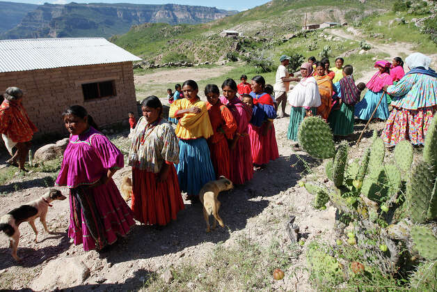 "Tarahumara women and men gather as corn is distributed in the settlement of Santa Rita in the Sierra Tarahumara near Batopilas, Mexico, Monday, Oct. 8, 2012. Pilar Pedersen, 59, of Alpine, Texas, solicited donation through advertisement placed in several Big Bend area newspapers. A frequent visitor to the area, she saw how the drought affected the Tarahumaras in the surrounding settlements. It was the second such trip she made with food donations. Last January, she was able to collect $6,000, enough to buy 10 metric tons of corn. ""The last time people were really hungry. There was no water, There had been no harvest. They'd used all their precious maize which is life to them,"" she said. The Batopilas government helps with the distribution of the corn. Photo: Jerry Lara, San Antonio Express-News / San Antonio Express-News"