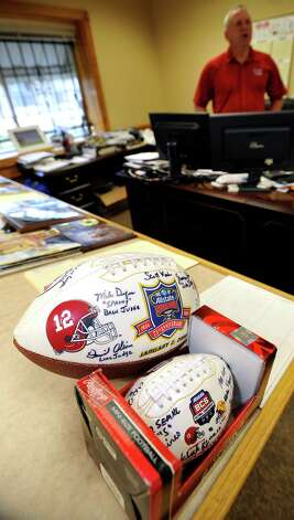 Two of his ball souvenirs sit on a table. The big one is from the 2009 Sugar Bowl where Alabama played Utah and the little ball is from the 2012 National Championship between the Alabama Crimsom Tide and LSU. Mike Defee is a football referee for the Big 12 conference. He lives in Mauriceville, and was at his office at Newtron Inc., Wednesday morning October 17, 2012, before he left for his next game in Reno Nevada later in the day.  Dave Ryan/The Enterprise