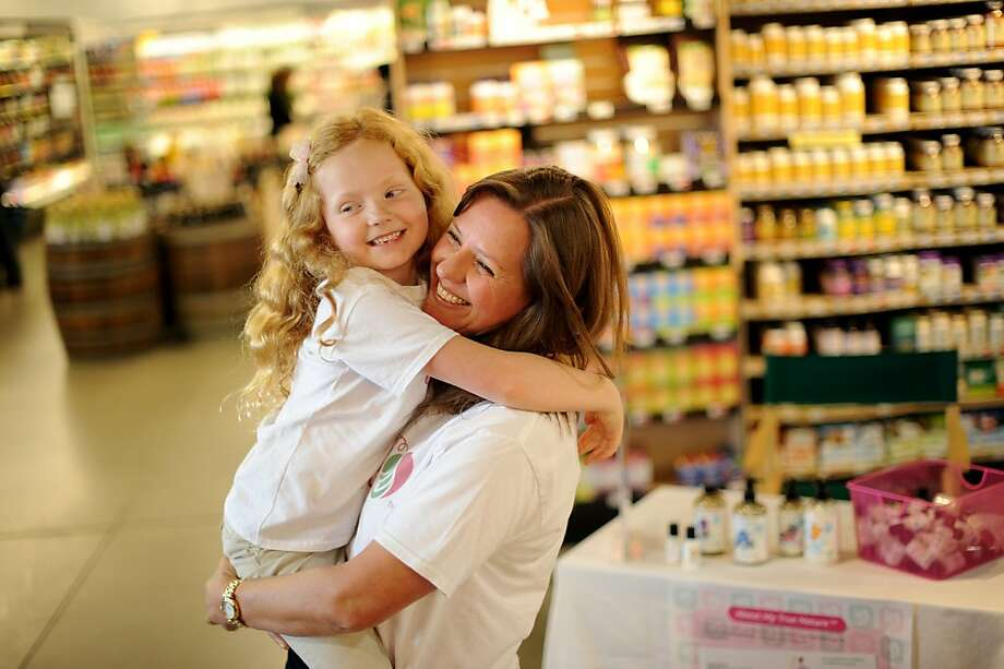 Kelly Boyd hugs her daughter Adeline, 6, while distributing samples at Berkeley Bowl. Photo: Noah Berger, Special To The Chronicle