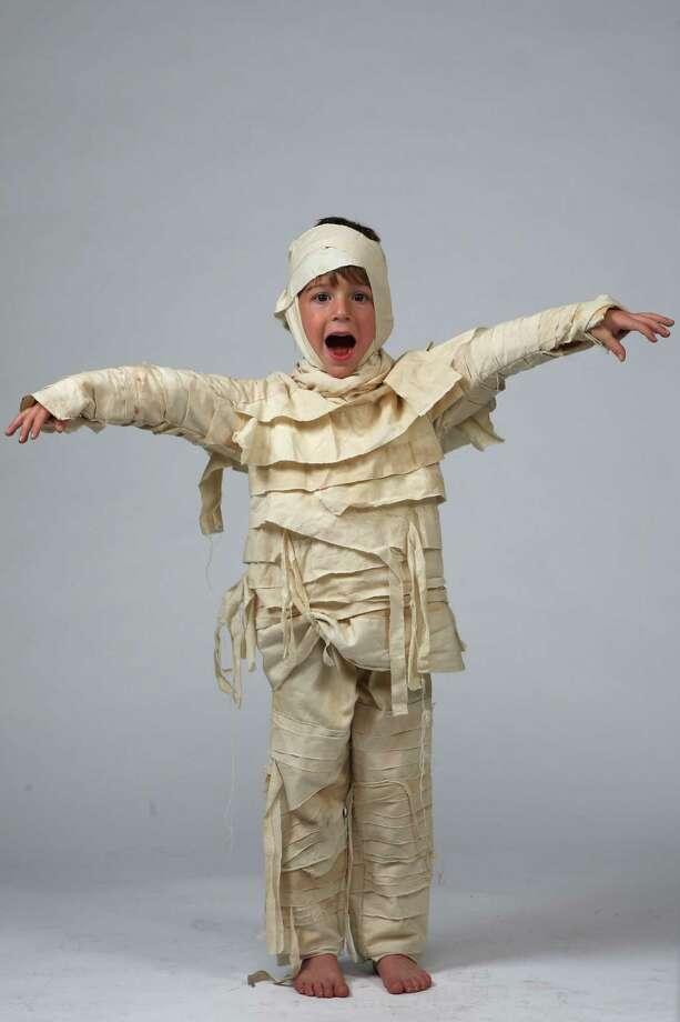 Ari Sutin models a mummy costume made last year by his mom, Miranda Sutin. Black tea bags were used to give white sheets that ancient look.  Photo: Jerry Lara, San Antonio Express-News / San Antonio Express-News
