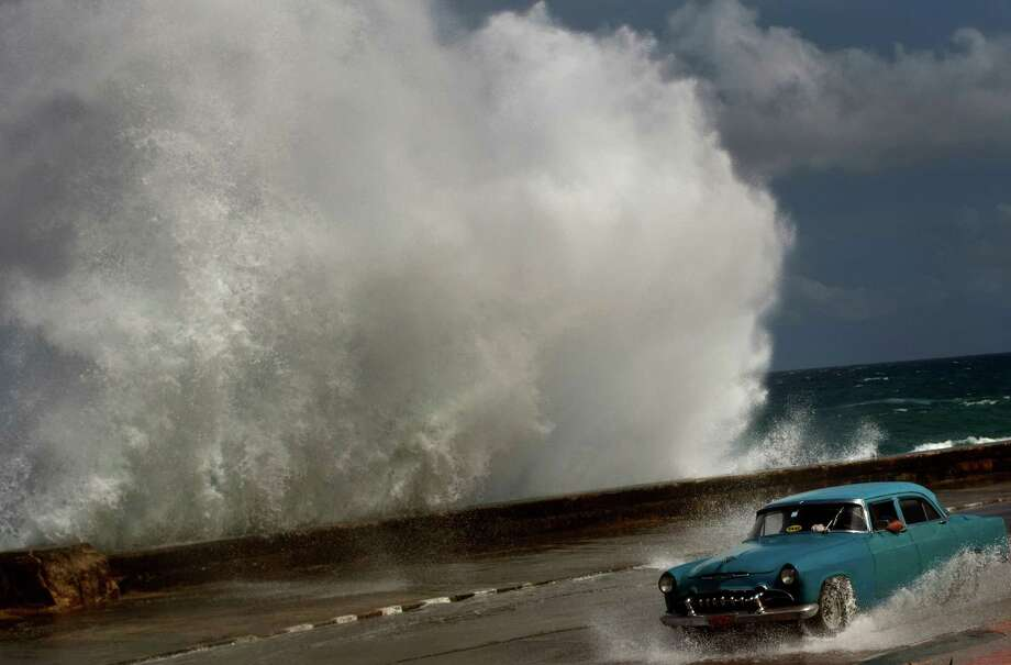 A driver maneuvers his classic American car along a wet road as a wave crashes against the Malecon in Havana, Cuba, Thursday, Oct. 25, 2012.  Hurricane Sandy blasted across eastern Cuba on Thursday as a potent Category 2 storm and headed for the Bahamas after causing at least two deaths in the Caribbean. Photo: Ramon Espinosa, Associated Press / AP