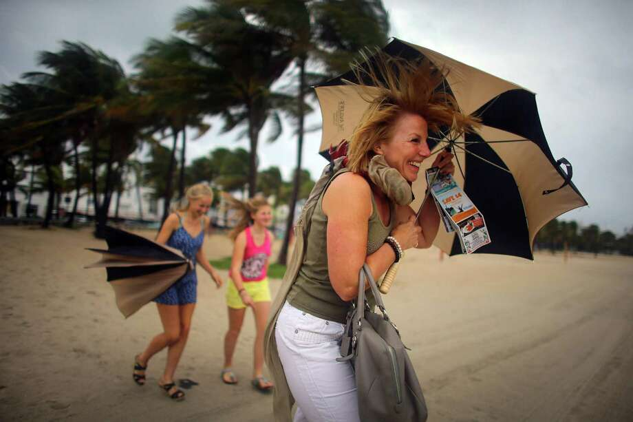 Laura Rath, on vacation from the Netherlands, walks on the beach with her family as they are buffeted by high winds of the outer bands of Hurricane Sandy on October 25, 2012 in Miami Beach, Florida. After passing over Jamaica Hurricane Sandy is expected to hit eastern Cuba and head into the Bahamas today and tomorrow. There is a tropical storm warning in place for coastal Miami-Dade, Broward, and Palm Beach Counties and the Atlantic waters off southeast Florida. Photo: Joe Raedle, Getty Images / 2012 Getty Images
