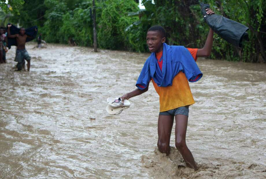 Residents wade through a street flooded by heavy rains from Hurricane Sandy in Port-au-Prince, Haiti, Thursday, Oct. 25, 2012. Photo: Dieu Nalio Chery, Associated Press / AP