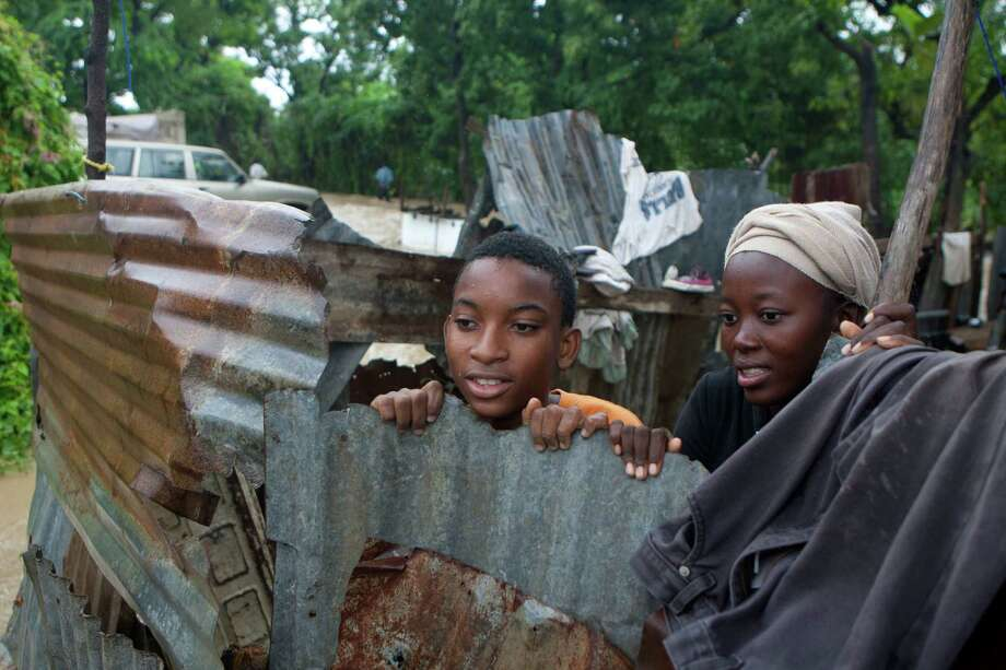 Residents look out on a street that was flooded by heavy rains from Hurricane Sandy in Port-au-Prince, Haiti, Thursday, Oct. 25, 2012. Photo: Dieu Nalio Chery, Associated Press / AP