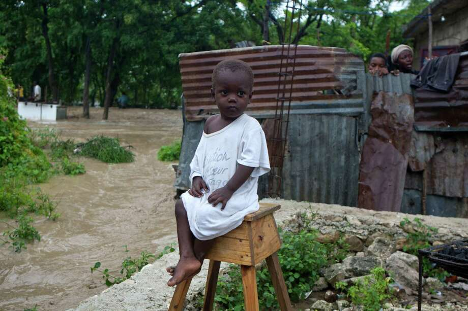 A young boy sits in front of his home, flooded by heavy rains from Hurricane Sandy in Port-au-Prince, Haiti, Thursday, Oct. 25, 2012. Photo: Dieu Nalio Chery, Associated Press / AP