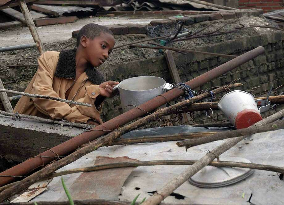 A Cuban child retrieves utensils from his home, demolished by Hurricane Sandy, on October 25, 2012 in Santiago de Cuba. Photo: MIGUEL RUBIERA JUSTIZ, AFP/Getty Images / AFP