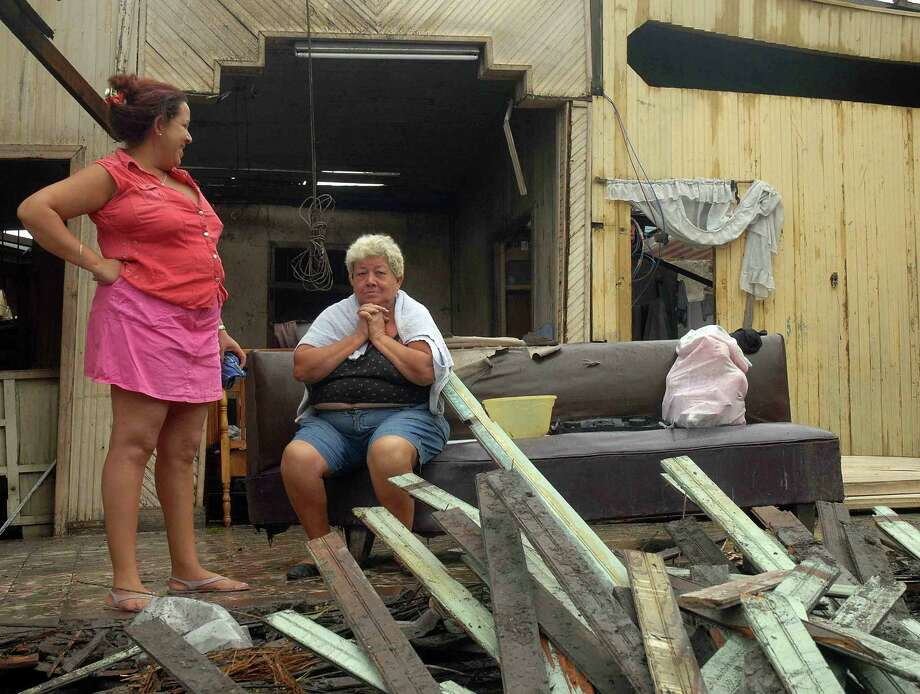 Two Cuban women remain inside their home, demolished by Hurricane Sandy, on October 25, 2012 in Santiago de Cuba. Photo: MIGUEL RUBIERA JUSTIZ, AFP/Getty Images / AFP