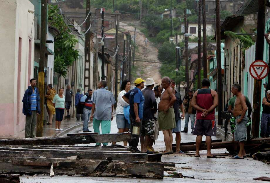 Residents inspect damage after the passing of Hurricane Sandy in Gibara, Cuba, Thursday, Oct. 25, 2012. Hurricane Sandy blasted across eastern Cuba on Thursday as a potent Category 2 storm and headed for the Bahamas after causing at least two deaths in the Caribbean. Photo: Franklin Reyes, Associated Press / AP