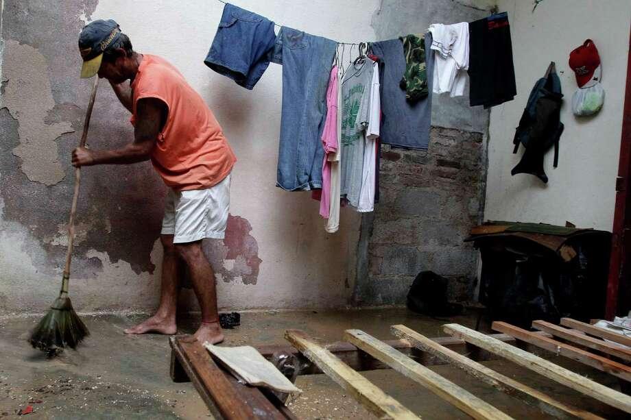 Jose Aguilera seeps his home's floor by his empty bed frame after the passing hurricane Sandy damaged his roof, causing rain to soak his mattress, in Gibara, Cuba, Thursday, Oct. 25, 2012. Hurricane Sandy blasted across eastern Cuba on Thursday as a potent Category 2 storm and headed for the Bahamas after causing at least two deaths in the Caribbean. Photo: Franklin Reyes, Associated Press / AP