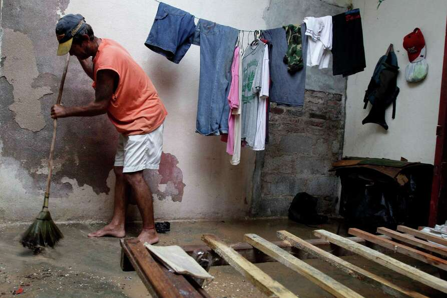 Jose Aguilera seeps his home's floor by his empty bed frame after the passing hurricane Sandy damage