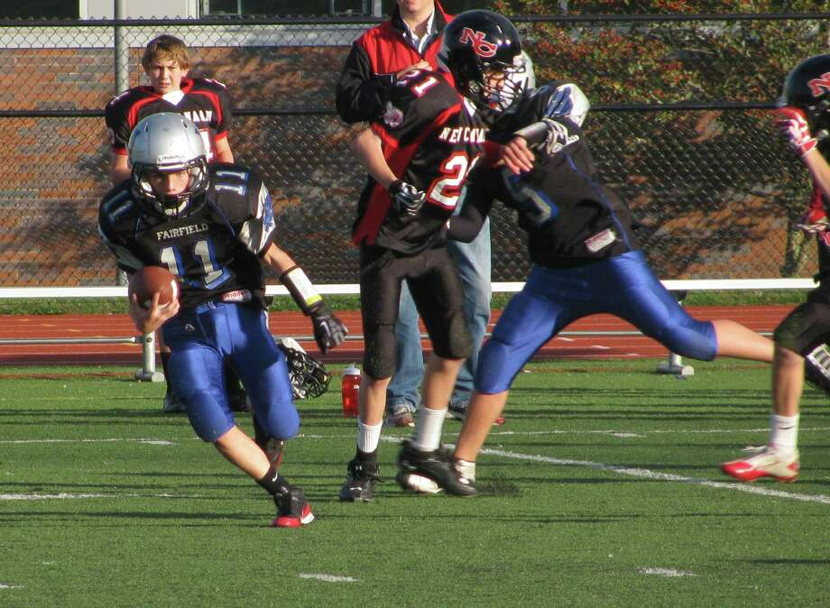 Fairfield Wildcats' seventh-grader Jack Hogarth runs the ball after one of his two interceptions during the Seventh Grade Team's 19-0 win over New Canaan on Saturday. Photo: Contributed Photo