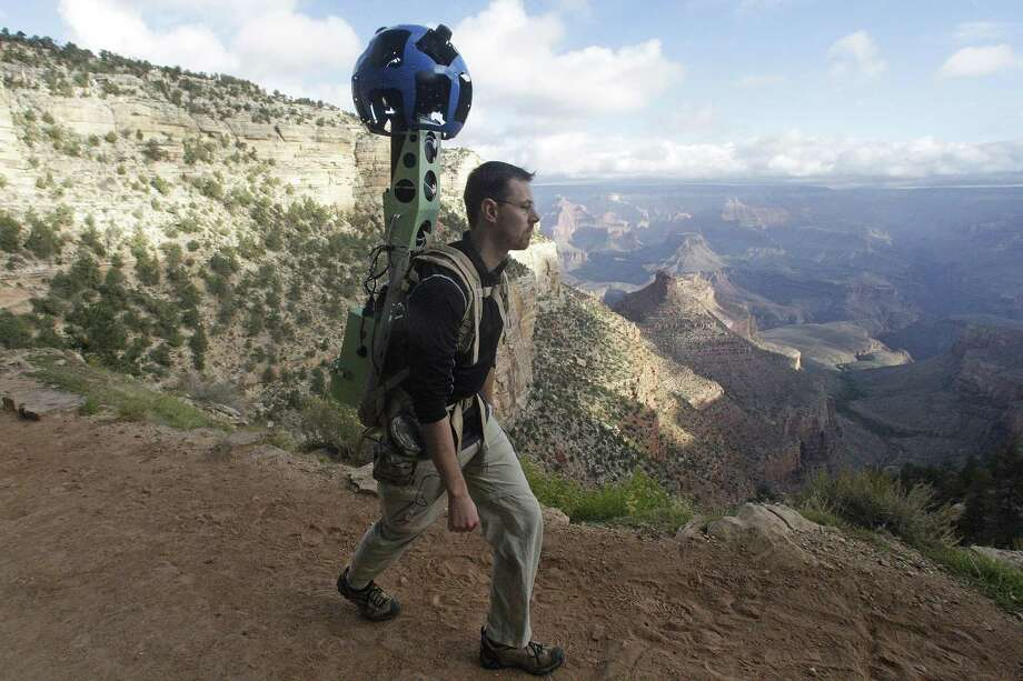 In this Monday Oct. 22, 2012, photo, Google product manager Ryan Falor walks with the Trekker during a demonstration for the media along the Bright Angel Trail at the South Rim of the Grand Canyon National Park in Arizona. The search engine giant is using the nearly 40-pound, backpack-sized camera unit to showcase the Grand Canyon's most popular hiking trails on the South Rim and other off-road sites. It's about 4 feet in height when set on the ground, and when worn, the camera system extends 2 feet above the operator's shoulders.  (AP Photo/Rick Bowmer) Photo: Rick Bowmer