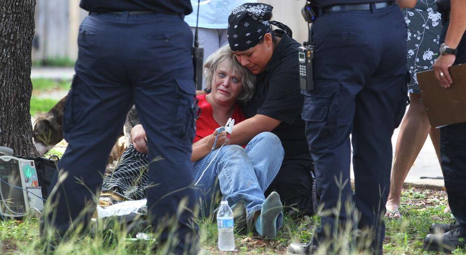 Paramedics treat Rachel Redfield, comforted by a friend and her son, for smoke inhalation. Photo: JOHN DAVENPORT, San Antonio Express-News / San Antonio Express-News