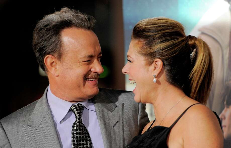 "Tom Hanks, left, a cast member in ""Cloud Atlas,"" look at his wife, actress Rita Wilson, in front of reporters at the premiere of the film at Grauman's Chinese Theatre on Wednesday, Oct. 24, 2012, in Los Angeles. Photo: Chris Pizzello, Associated Press / Invision"