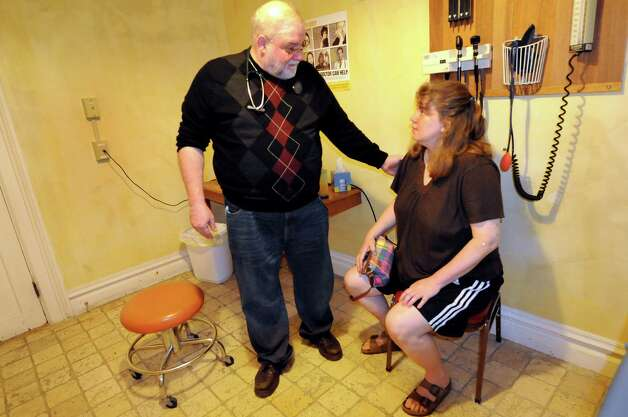 Following treatment, Dr. Bob Paeglow, left, prays with Anna Thompson of Poestenkill for her health on Friday, May 20, 2011, at Koinonia Primary Care in Albany, N.Y. (Cindy Schultz / Times Union archive) Photo: Cindy Schultz / 00013229A